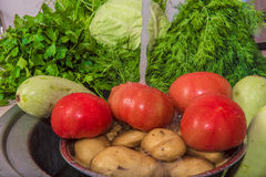 Vegetables food kitchen sink wet red organic fruits tomato domes. Preparation a useful vegetarian dish by a dinner Stock Image