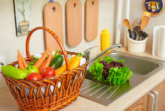 Vegetables and fresh greens in basket in kitchen interior, healthy food concept Royalty Free Stock Images