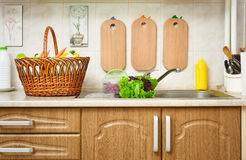 Vegetables and fresh greens in basket in kitchen interior, healthy food concept Stock Photography