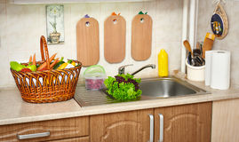 Vegetables and fresh greens in basket in kitchen interior, healthy food concept Stock Photo