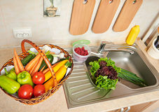 Vegetables and fresh greens in basket in kitchen interior, healthy food concept, top view Royalty Free Stock Photo