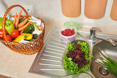 Vegetables and fresh greens in basket in kitchen interior, healthy food concept, top view Stock Images
