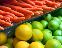 Vegetables and fruit on the counter in the store. Carrots, grapefruit and apples in the produce store Stock Photo