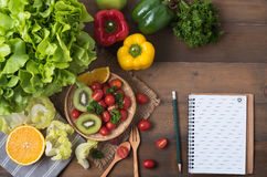 Vegetables and fruit with notebook on wood background Royalty Free Stock Photo