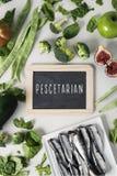 Vegetables, fruit, sardines and text pescetarian stock photos