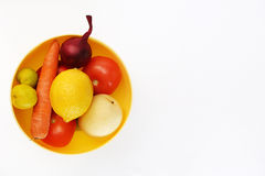 Vegetables and fruit on a white background. Vegetables and fruits in a yellow plate Stock Image