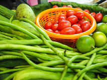 Vegetables and fruits on banana leaf. Tomatoes, cow-peas, lemons cucumbers and mangoes are placed on basket which is covered by banana leaf. They are food Stock Images