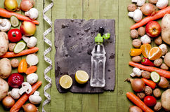 Vegetables and fruits, bottle of water on a wooden background an Royalty Free Stock Image