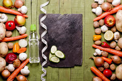Vegetables and fruits, bottle of water on a wooden background an Royalty Free Stock Photography