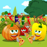 Vegetables and fruits eating pizza on a meadow Royalty Free Stock Images