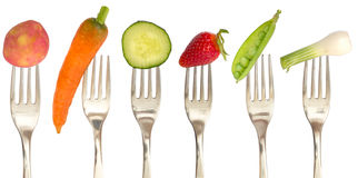 Vegetables and fruits on the forks Royalty Free Stock Photos