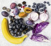 Vegetables and fruits rich in vitamin anthocyanin: bananas, blueberries, red cabbage, sweet purple onions, dark grapes. Prunes. Benefits of nutrition for the stock image