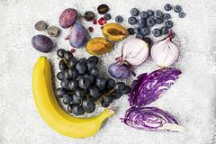 Vegetables and fruits rich in vitamin anthocyanin: bananas, blueberries, red cabbage, sweet purple onions, dark grapes. Prunes. Benefits of nutrition for the royalty free stock photos