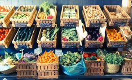 Vegetables and fruits in wicker baskets in greengrocery royalty free stock photography