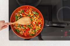 Vegetables are in a frying pan. Woman cooking colourful fresh vegetables on an electric stove. stock photos
