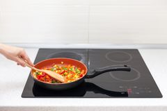 Vegetables are in a frying pan. Woman cooking colourful fresh vegetables on an electric stove. Vegetables are in a frying pan. Woman cooking colourful fresh stock image