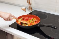 Vegetables are in a frying pan. Woman cooking colourful fresh vegetables on an electric stove. stock photo