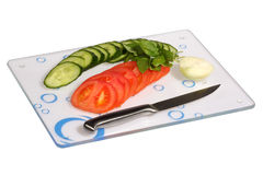 Vegetables on a glass cutting board. Cucumbers, onions, tomatoes on a glass cutting board over white background Royalty Free Stock Image