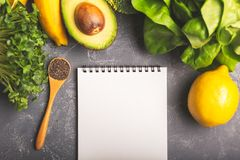 Vegetables, greens and a notepad on grey background royalty free stock image