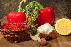 Vegetables with the herb. Red paprika, sliced lemon, garlic and fresh herb on the wooden table Royalty Free Stock Photo