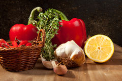 Vegetables with the herb. Red paprika, sliced lemon, garlic and fresh herb on the wooden table Stock Photo