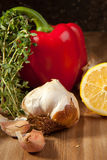 Vegetables with the herb. Red paprika, sliced lemon, garlic and fresh herb on the wooden table Stock Photography