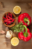 Vegetables with the herb. Red paprika, sliced lemon and fresh herb on the wooden table Royalty Free Stock Images