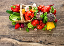 Vegetables and herbs in basket on wooden background Stock Images