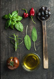 Vegetables and herbs on dark rustic wooden background. Greek black olives, fresh green sage, rosemary, basil herbs, oil Stock Images