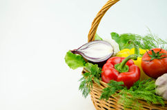 Vegetables and herbs in a wicker basket Stock Photos