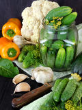 Vegetables and ingredients are prepared for conservation. Peppers, cucumbers and cauliflower on a dark table Royalty Free Stock Photos