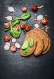 Vegetables ingredients for vegetarian sandwich  on dark wooden background. Top view Stock Images