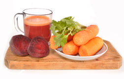Vegetables for juice. Beet, carrots, juice glass stand on a wooden board Royalty Free Stock Photos