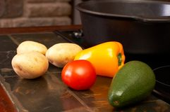 Vegetables on kitchen counter. Potatoes, red pepper, tomato and avocado shot on the kitchen counter next to the iron pot Royalty Free Stock Photo
