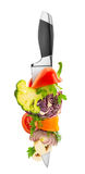 Vegetables on kitchen knife Stock Photos
