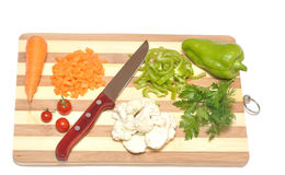 Vegetables and kitchen-knife on cutting board Stock Images
