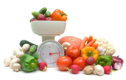 Vegetables and kitchen scales on white background Royalty Free Stock Images