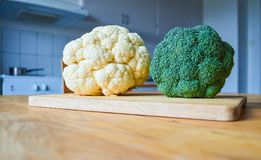 Broccoli and cauliflower on chopping board on wooden table stock images