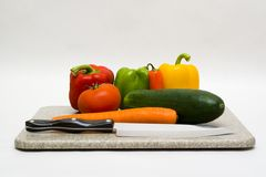 Vegetables with a knife. A cutting board with vegetables and a knife Stock Image