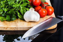 Vegetables and a knife on a cutting board. Some cherry tomatoes, parsley and garlic on a cutting board  over a dark surface Stock Photo