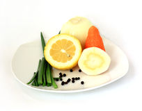 Vegetables and lemon. The cleared onions, green onions, carrots, root of parsley and half lemon on a white plate. Horizontally Royalty Free Stock Photography