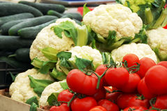 Vegetables on market. Red tomatoes, cauliflowers and cucumbers on market stand outdoor Stock Image