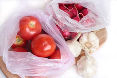Vegetables from the market. Tomatoes and garden radish in a package, three heads of garlic. Horizontal photo Stock Image