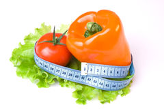 Vegetables and measure tape. Paprika and tomato binded with a measure tape Royalty Free Stock Photos