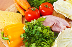 Vegetables, meat, cheese on wooden chopping board Royalty Free Stock Photo