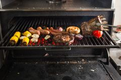 Vegetables and meat on the grill on hot coals with smoke royalty free stock photo