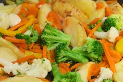 Vegetables mix. Closeup of fried new potatoes with vegetables: auliflower, broccoli, garlic, carrot, red pepper etc stock photography