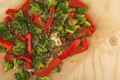 Vegetables mix baked in the oven on paper on the wooden table. Royalty Free Stock Image