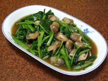 Vegetables And Mushrooms. A plate of fried spinach with straw mushrooms Stock Images
