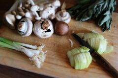 Vegetables Mushrooms and Knife on Wooden Board Stock Photography